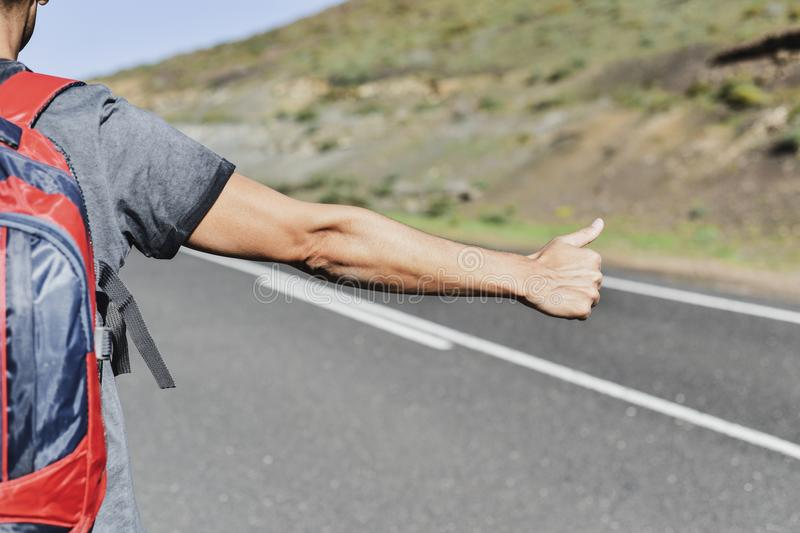 Young backpacker man hitchhiking. Closeup of a young caucasian man, seen from behind, carrying a backpack hitchhiking in a secondary road, with his thumb up royalty free stock photos