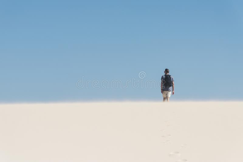 Young backpacker man walking by the desert. A young caucasian man, seen from behind, wearing a t-shirt and shorts, and carrying a backpack, walking by a white royalty free stock images