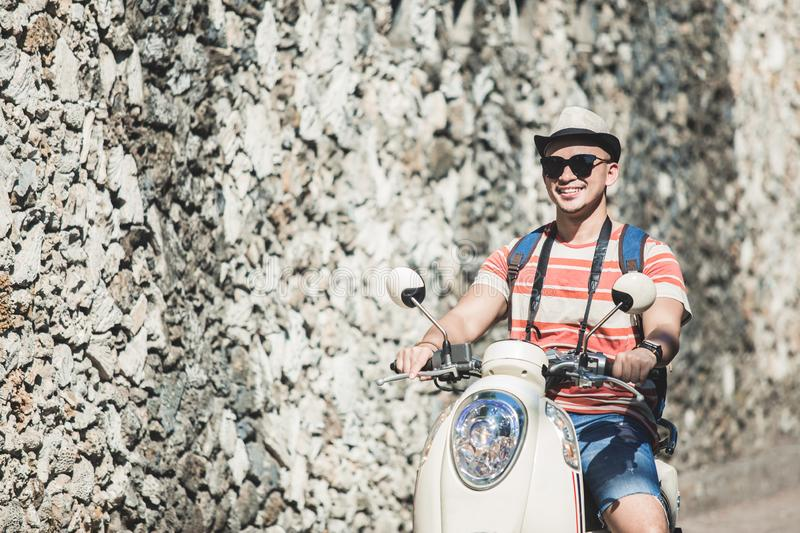 Young backpacker riding motorbike during vacation on sunny day. Portrait of young backpacker riding motorbike during vacation on sunny day stock images