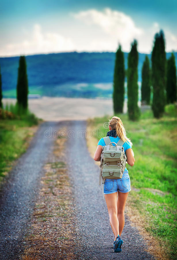 Young backpacker traveling along Europe. Happy female walking in the park, discovering world, summer vacation concept royalty free stock image