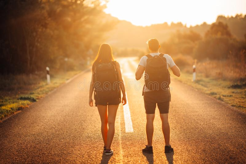 Young backpacking adventurous couple hitchhiking on the road.Adventure of life.Travel lifestyle.Low budget traveling.Adventurous stock photography
