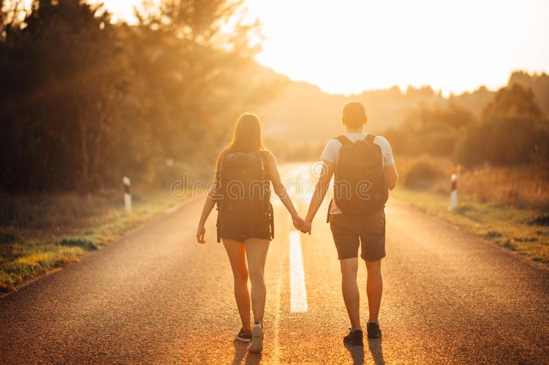 Young backpacking adventurous couple hitchhiking on the road.Stopping transportation.Travel lifestyle.Low budget traveling stock images