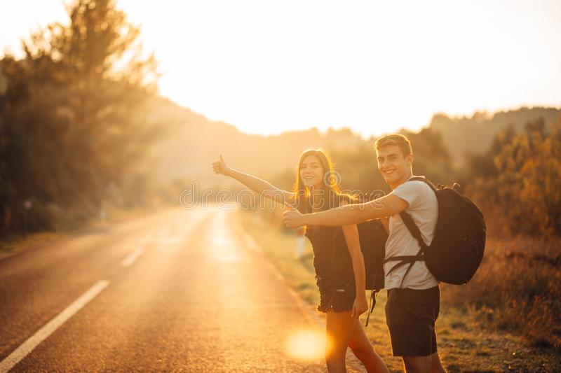 Young backpacking adventurous couple hitchhiking on the road.Stopping transportation.Travel lifestyle.Low budget traveling. Adventurous active vacations royalty free stock photography