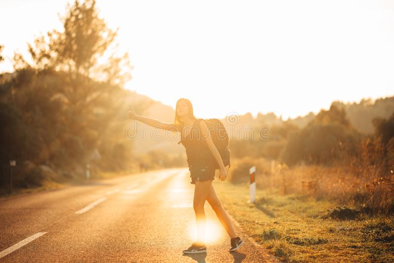 Young backpacking adventurous woman hitchhiking on the road.Ready for adventure of life.Travel lifestyle.Low budget traveling.Adve. Nturous active vacations stock images