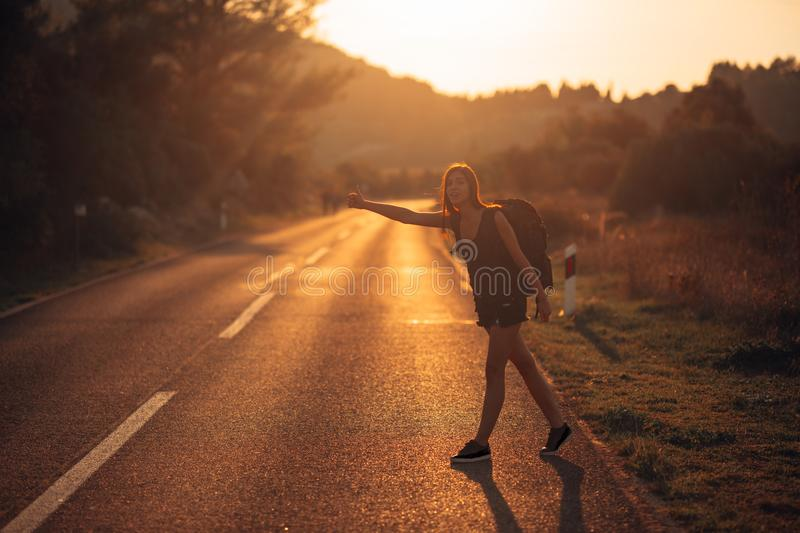 Young backpacking adventurous woman hitchhiking on the road.Ready for adventure of life.Travel lifestyle.Low budget traveling.Adve royalty free stock photography