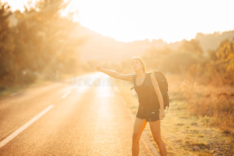 Young backpacking adventurous woman hitchhiking on the road. Stopping a car with a thumb. Travel lifestyle. Low budget traveling. Adventurous active vacations stock photography