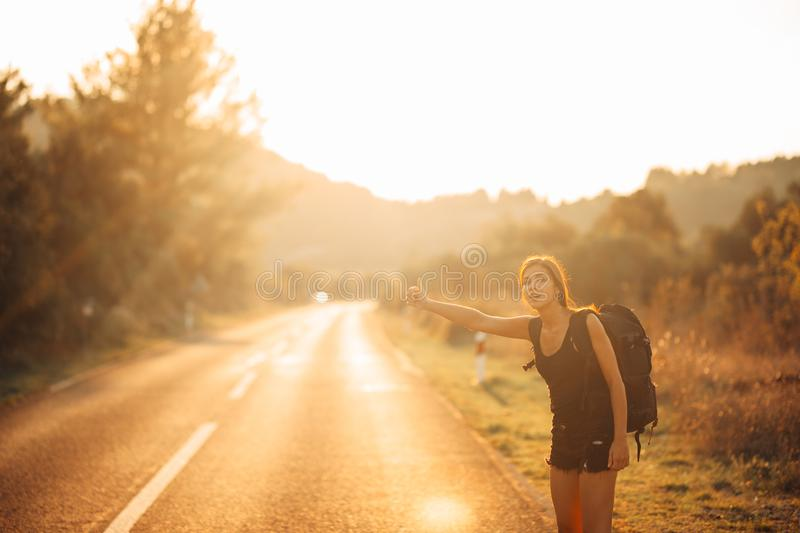 Young backpacking adventurous woman hitchhiking on the road.Stopping a car with a thumb.Travel lifestyle.Low budget traveling. Adventurous active vacations stock photos