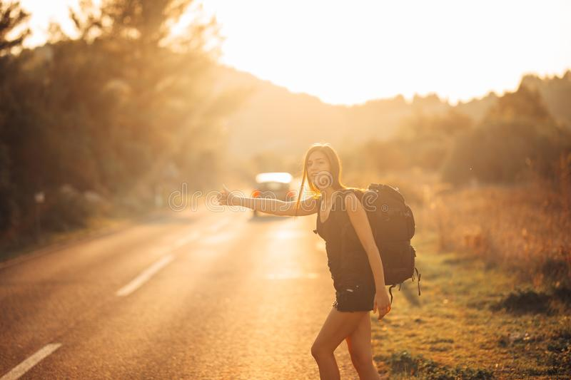 Young backpacking adventurous woman hitchhiking on the road. Stopping a car with a thumb. Travel lifestyle. Low budget traveling. Adventurous active vacations royalty free stock image