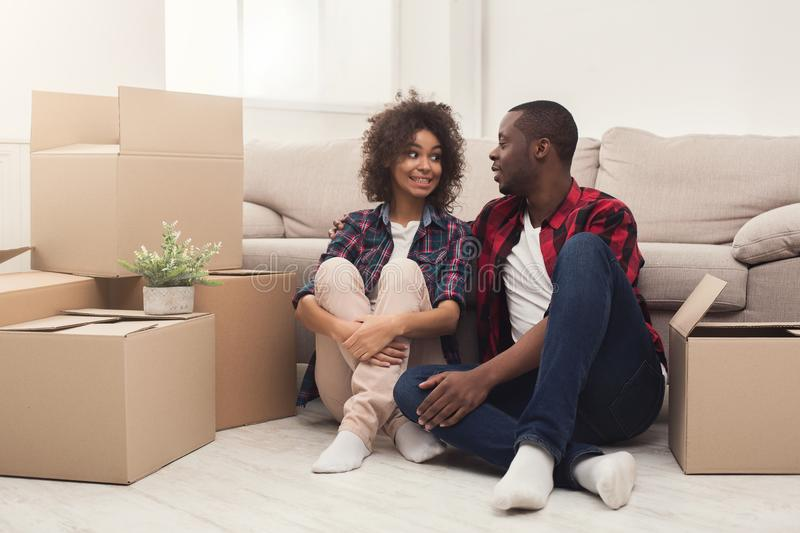 Young balck couple unpacking moving boxes stock photography