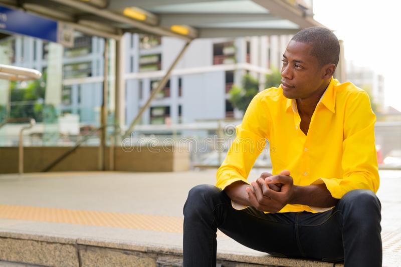 Young bald African businessman thinking and sitting outside the subway train station stock images