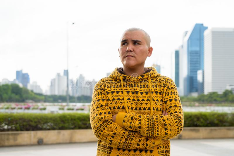 Young bald Asian man against view of the city at the park stock photos