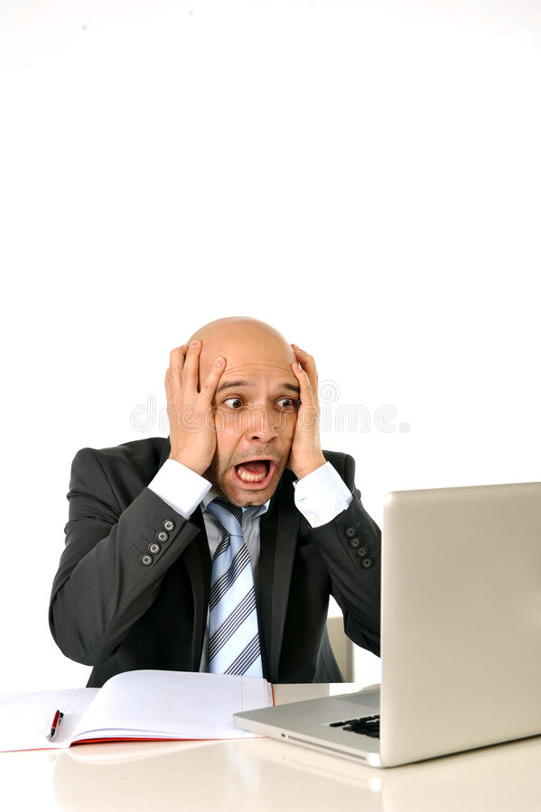 Young bald attractive business man desperate with computer at work stock photography