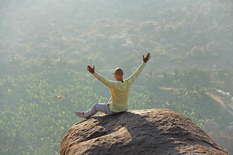 A young bald man raised his hands and greeted the sun on the top royalty free stock photo