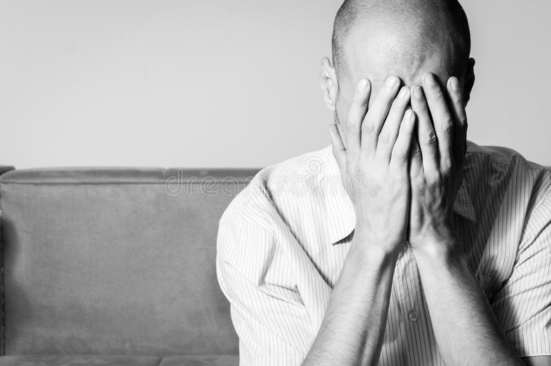 Young bald man in the shirt feeling depressed and miserable cover his face with his hands and cry in his room black and white. royalty free stock photo