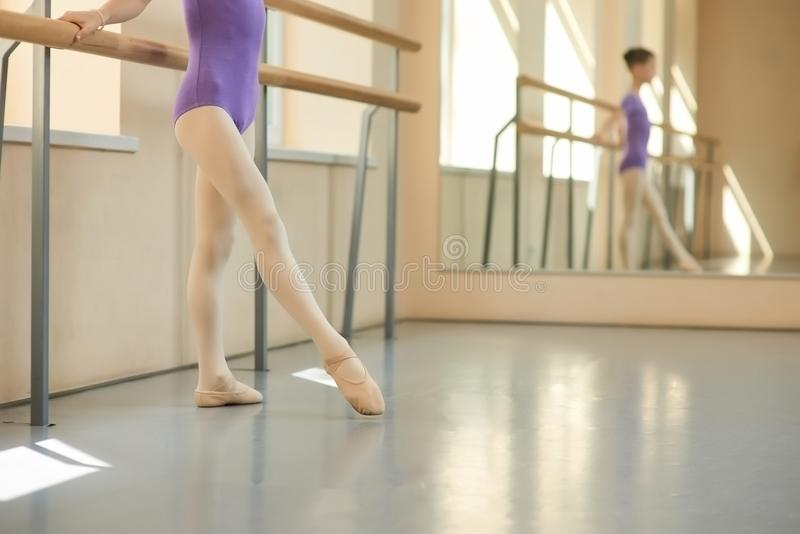 Young ballerina in ballet hall, cropped image. Girl standing near barre in ballet studio in ballet shoes royalty free stock image
