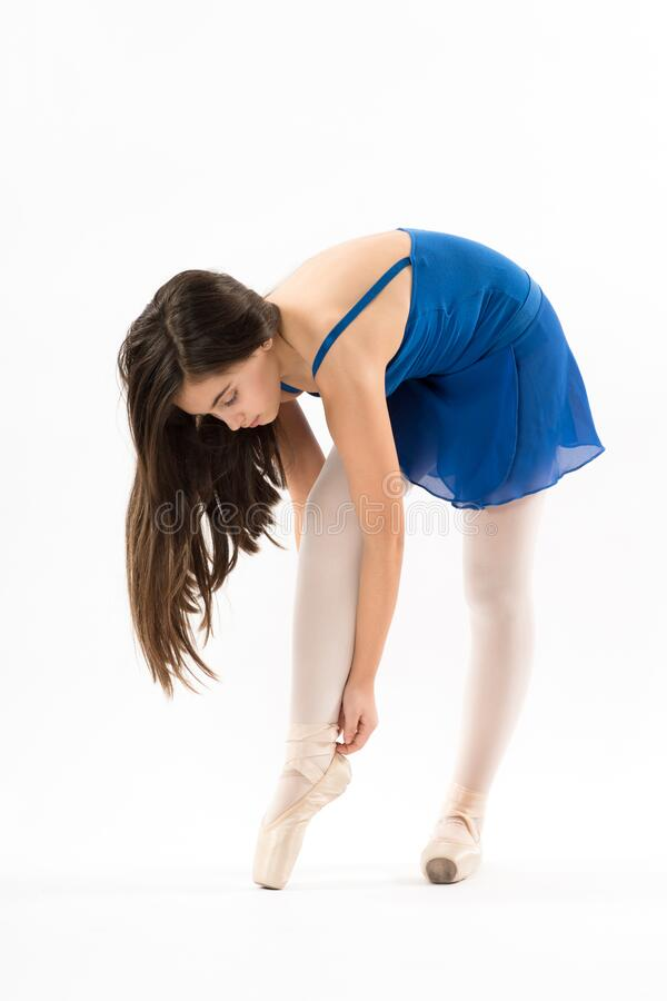 Young ballerina bending down tying her shoes. Young ballerina bending down tying her pink ballet shoes with her long hair hanging free over her shoulder isolated stock images