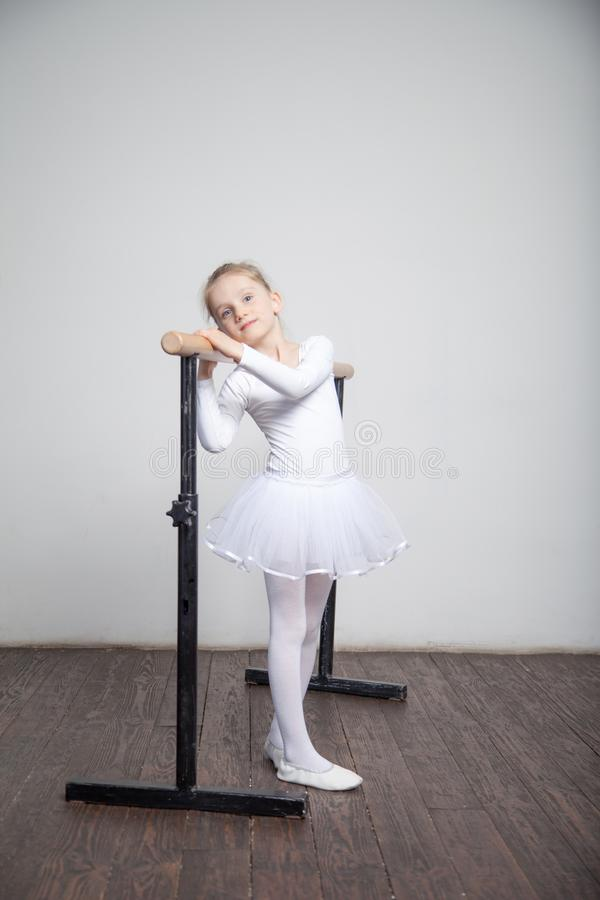 Young ballerina girl in a white tutu. Adorable child dancing classical ballet in a white studio with wooden floor. Children dance. stock image