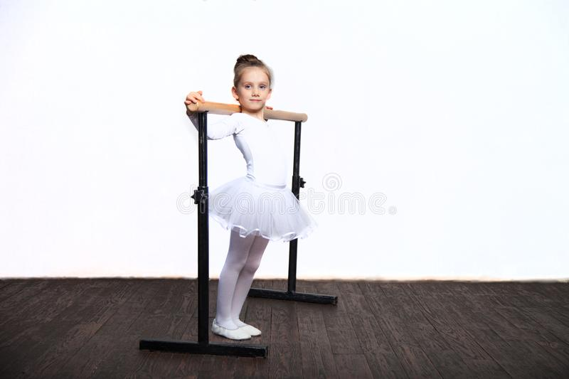 Young ballerina girl in a white tutu. Adorable child dancing classical ballet in a white studio with wooden floor. Children dance. stock images