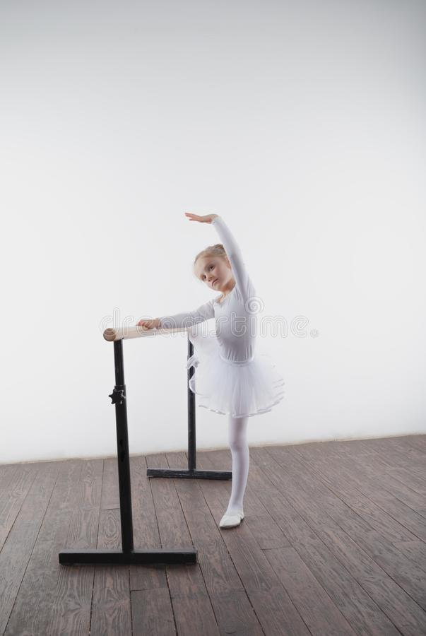 Young ballerina girl in a white tutu. Adorable child dancing classical ballet in a white studio with wooden floor. Children dance. stock photos