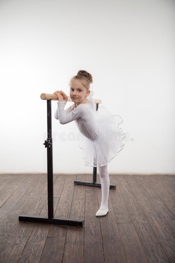 Young ballerina girl in a white tutu. Adorable child dancing classical ballet in a white studio with wooden floor. Children dance. stock photo