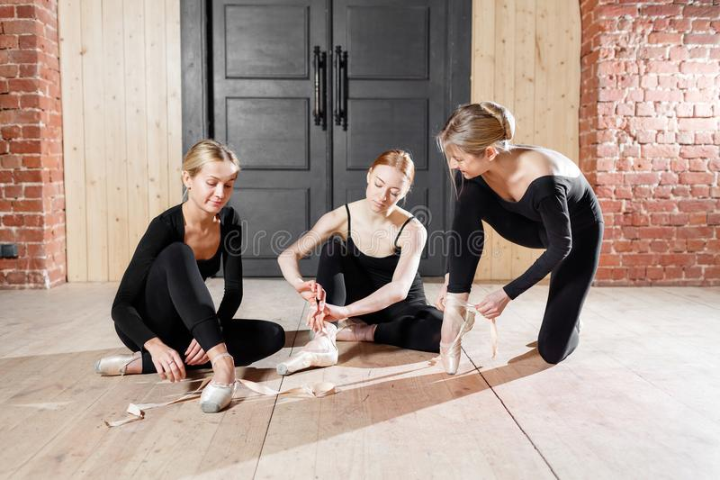 Pointe shoes. Young ballerina girls. Women at the rehearsal in black bodysuits. Prepare a theatrical performance. Young ballerina girls. Women at the rehearsal stock images