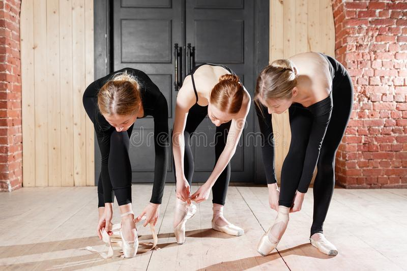 Pointe shoes. Young ballerina girls. Women at the rehearsal in black bodysuits. Prepare a theatrical performance. Young ballerina girls. Women at the rehearsal royalty free stock photos
