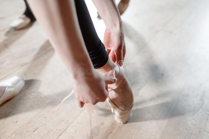 The ballet concept. Pointe shoes close up. Young ballerina girls. Women at the rehearsal in black bodysuits. Prepare a. Young ballerina girls. Women at the stock photos