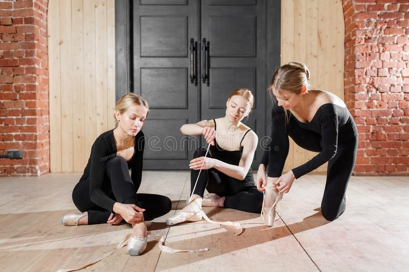 Pointe shoes. Young ballerina girls. Women at the rehearsal in black bodysuits. Prepare a theatrical performance. Young ballerina girls. Women at the rehearsal stock image