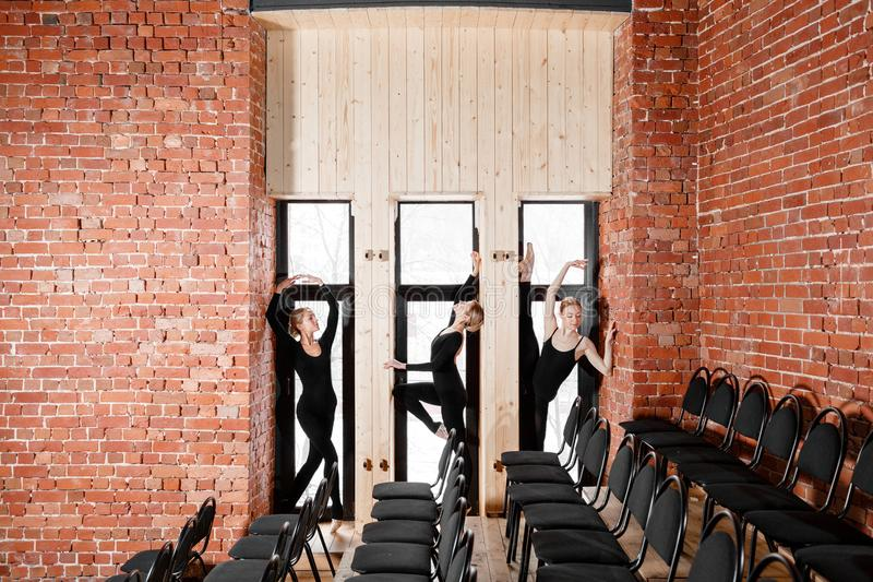 Young ballerina girls. Women at the rehearsal in black bodysuits. Prepare a theatrical performance. Three persons. Brick walls and interior in loft style royalty free stock photo