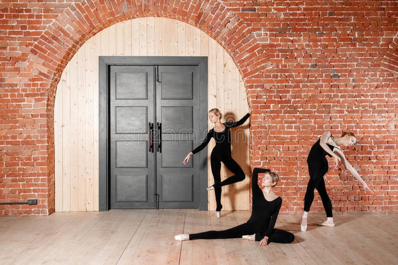 Young ballerina girls. Women at the rehearsal in black bodysuits. Prepare a theatrical performance. Three persons. Brick walls and interior in loft style stock photos