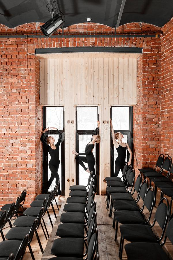 Young ballerina girls. Women at the rehearsal in black bodysuits. Prepare a theatrical performance. Three persons. Brick walls and interior in loft style royalty free stock image