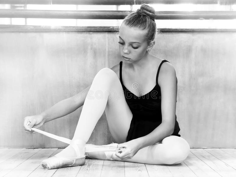 Young ballerina in the hall for rehearsals. Black and white photo. Ballet. Dancing. stock photos