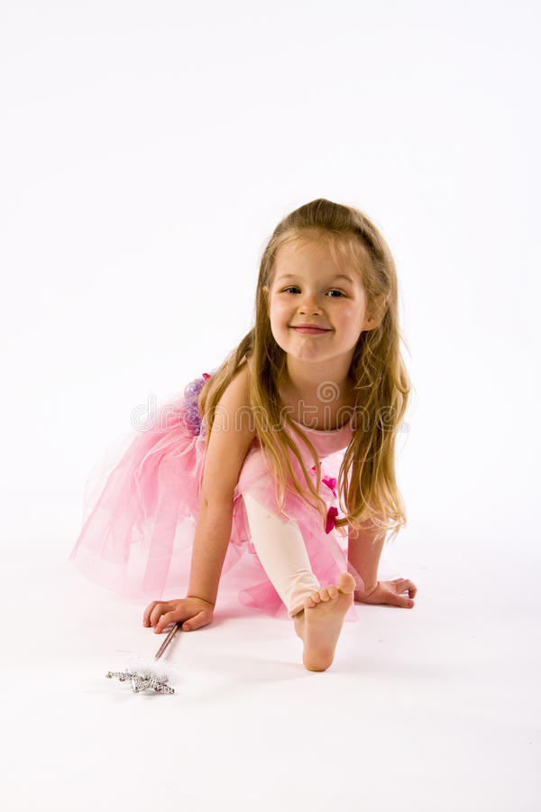 Young ballerina kneels and smiles at camera. stock image