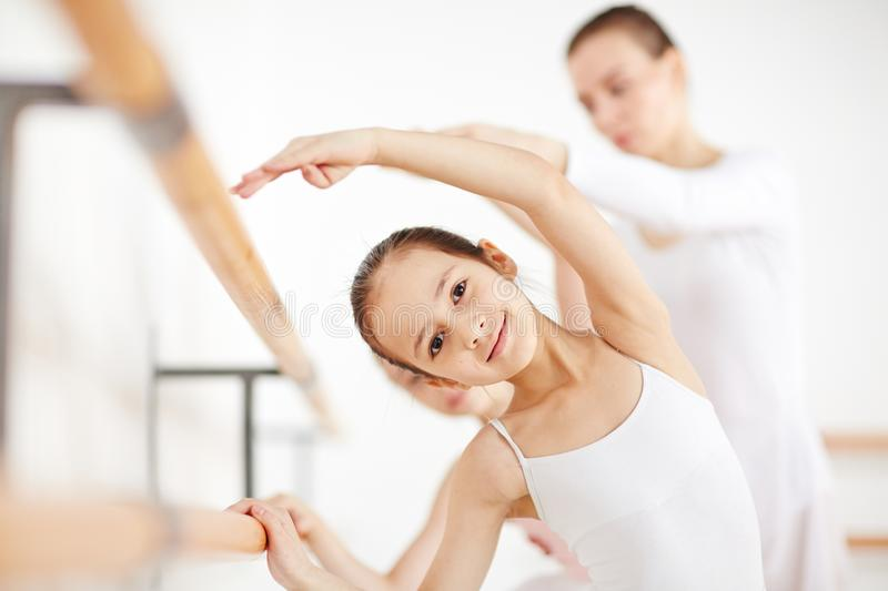Beautiful girl making position in dancing school. Young ballerina learning movements with hand up at wooden machine and looking at camera royalty free stock photography