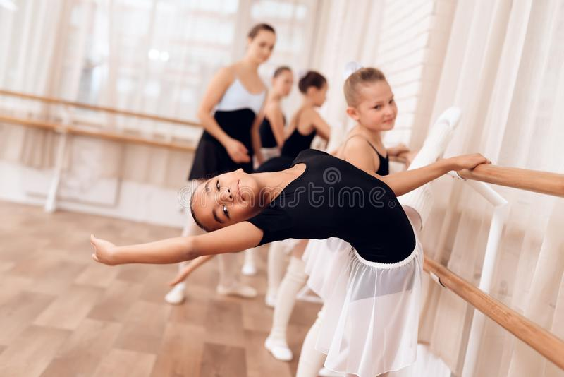 The young ballerina makes a dance movement with her hands during a class at a ballet school. The trainer of the ballet school helps young ballerinas perform stock images