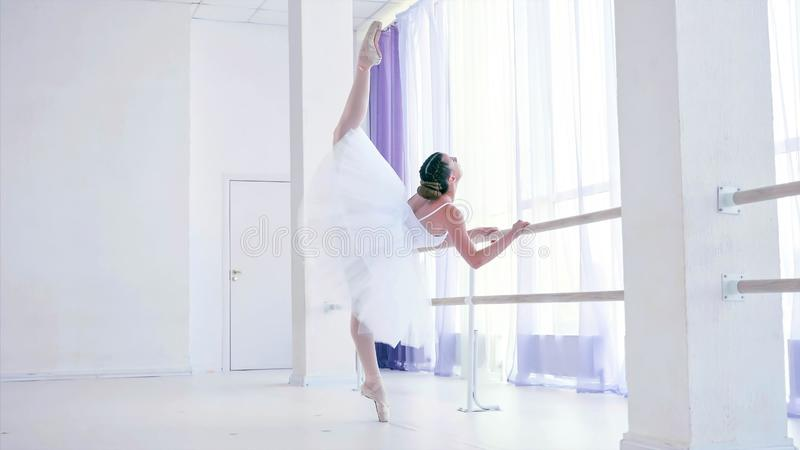 Young ballerina is training ballet element near the barre stand in dance class. stock image