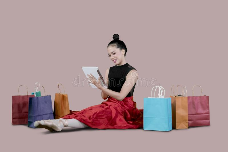 Young ballerina using a digital tablet for shopping online royalty free stock photo