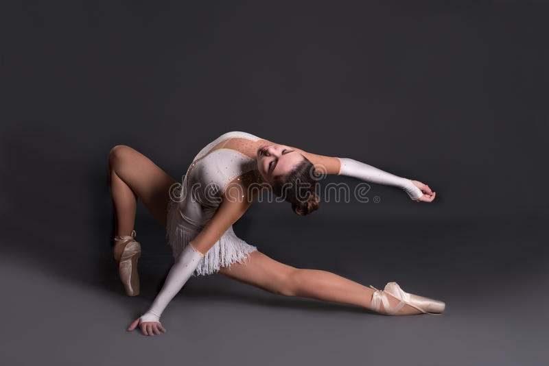 The young ballerina in white pointes dances royalty free stock image
