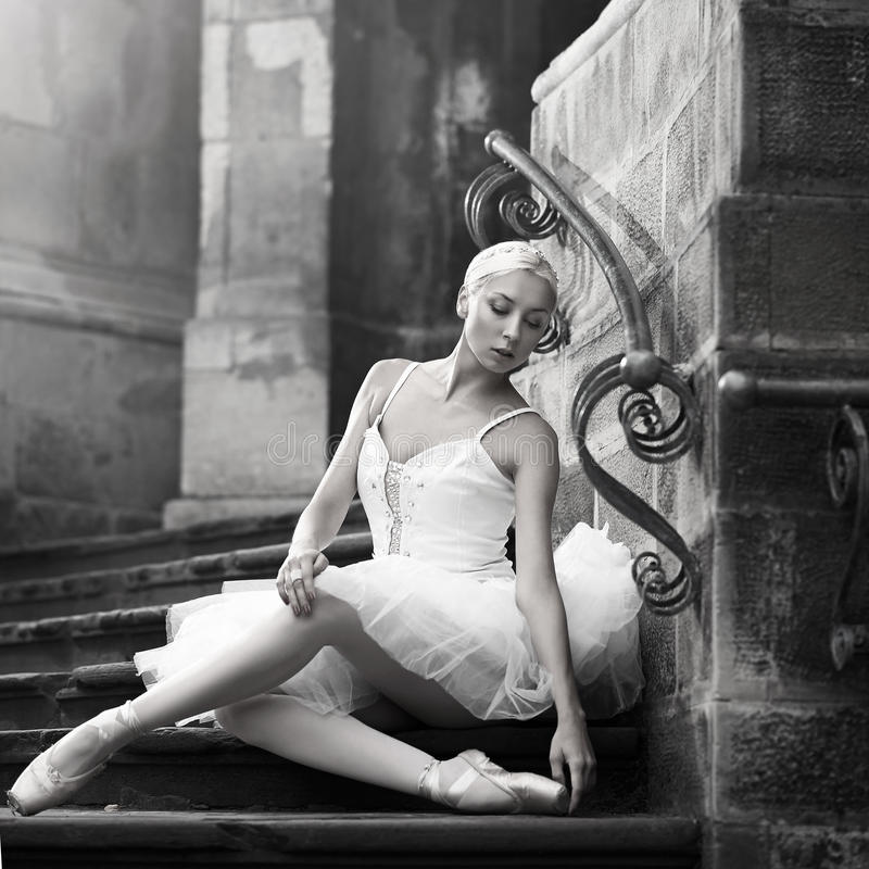 Young ballerina woman posing on stairs stock photo