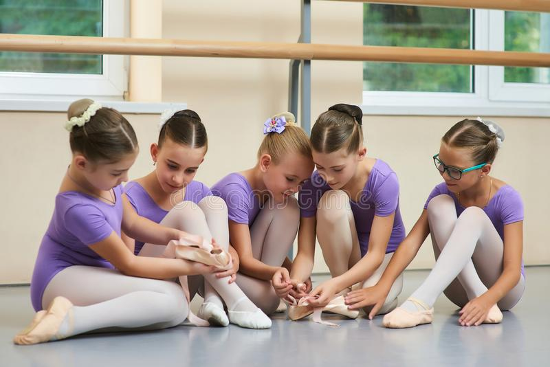 Young ballerinas at classical dance school. Young beautiful ballet dancers sitting on the floor. Kids having break royalty free stock photos