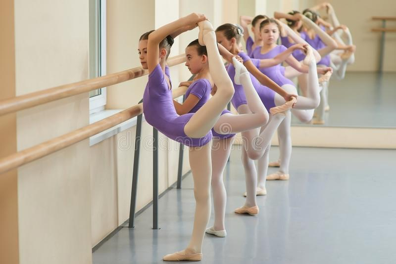Young ballerinas doing exercises in studio. stock photo