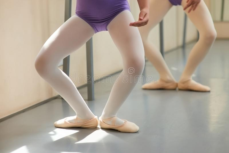 Young ballerinas having practice, cropped image. Legs of two little girls dancing at classical ballet studio. Basic ballet position stock photo