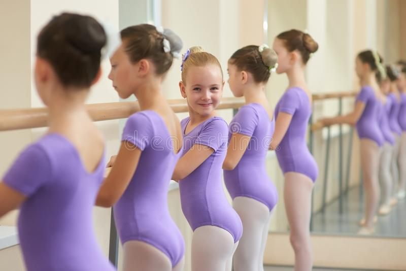 Young ballerinas rehearsing near ballet barre. royalty free stock photography