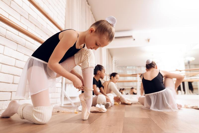 Young ballerinas rest during a break in the ballet classes. The girls communicate with each other at the ballet school. They want to become dancers royalty free stock photography