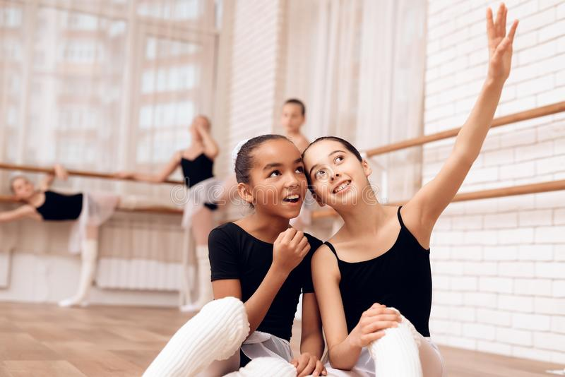 Young ballerinas rest during a break in the ballet classes. The girls communicate with each other at the ballet school. They want to become dancers stock image