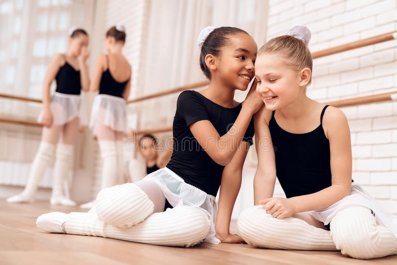 Young ballerinas rest during a break in the ballet classes. The girls communicate with each other at the ballet school. They want to become dancers royalty free stock photo