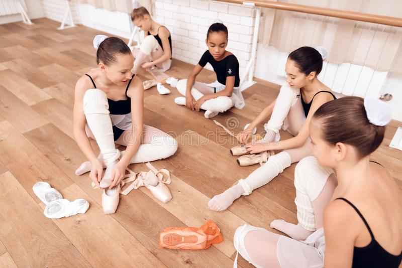 Young ballerinas rest during a break in the ballet classes. The girls communicate with each other at the ballet school. They want to become dancers royalty free stock photos