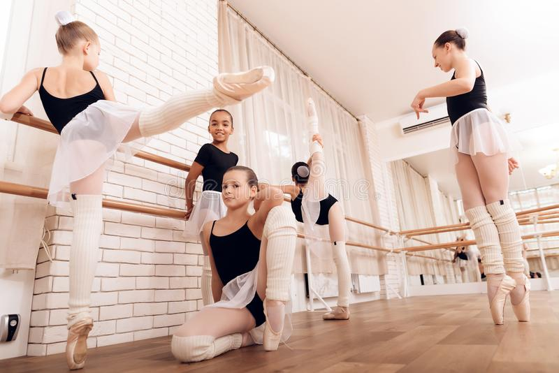 Young ballerinas rest during a break in the ballet classes. The girls communicate with each other at the ballet school. They want to become dancers royalty free stock images
