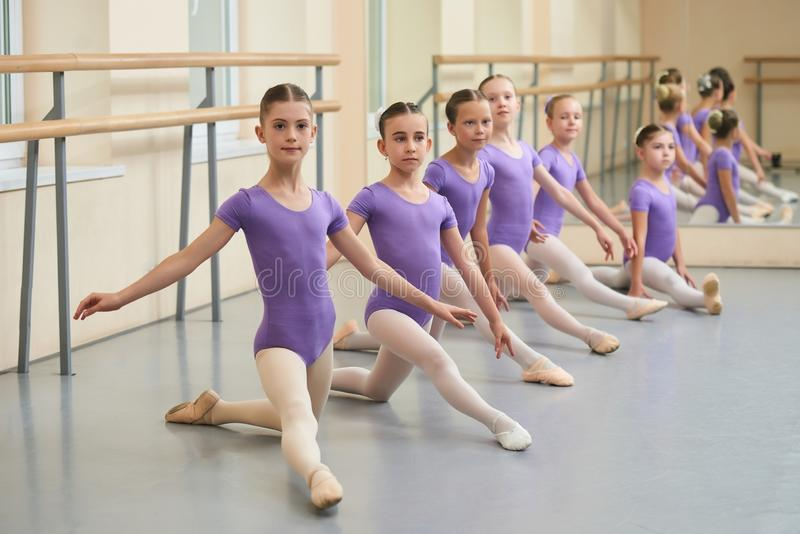 Young ballerinas stretching on the floor. royalty free stock photos