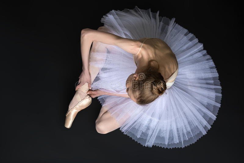 Young ballet dancer tying pointe sitting on the stock photos